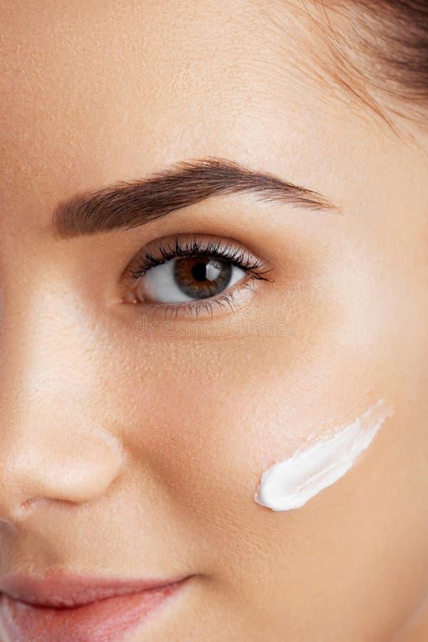 Face bonita da mulher Hábitos de Skincare Face da mulher nova Menina que toma de sua tez seca que aplica o creme hidratando foto de stock