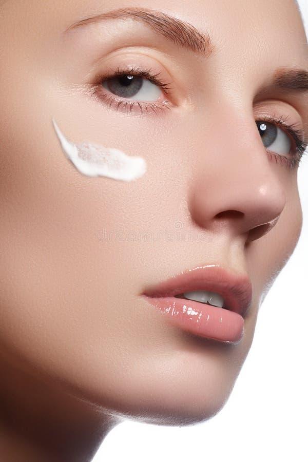 Face bonita da mulher nova com creme cosmético em um mordente fotos de stock