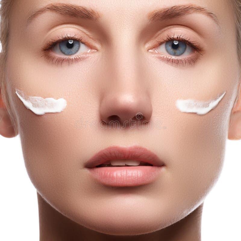 Face bonita da mulher nova com creme cosmético em um mordente Conceito do cuidado de pele Retrato do close up isolado no branco C foto de stock