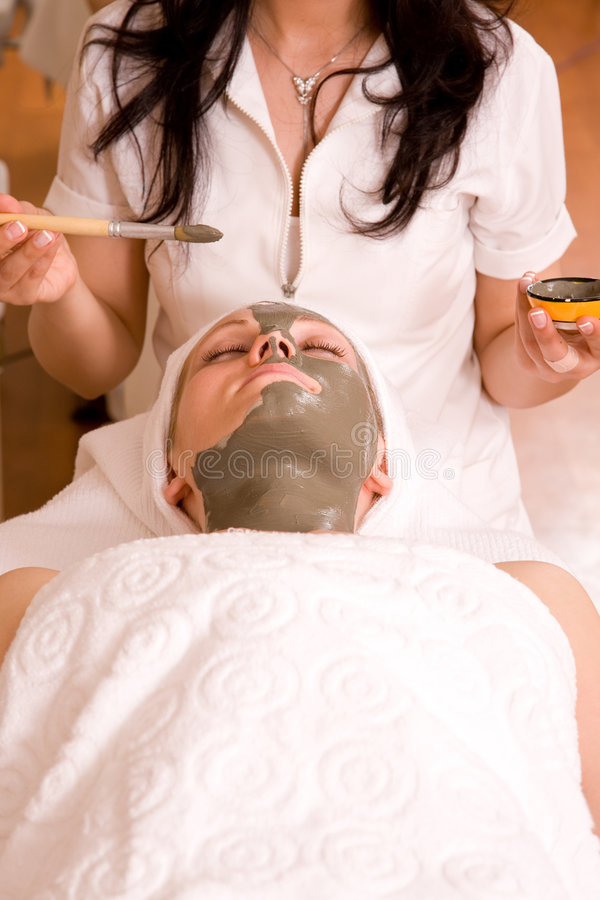 Face care. Beautiful woman having a face care session at spa center stock image
