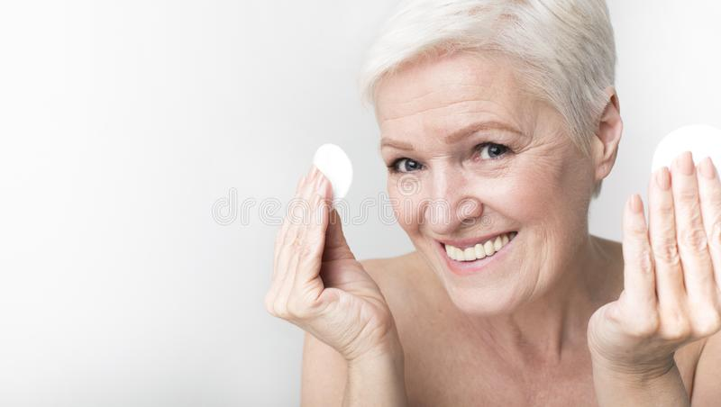 Portrait of positive senior woman with cotton pads royalty free stock images