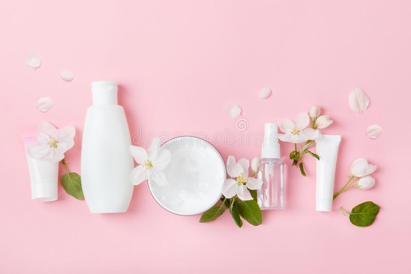 Face care products tonic or lotion, serum, cream, micellar water, cotton pads, shaver on pink background with spring apple bloss. Om. Freshness natural anti-age stock images
