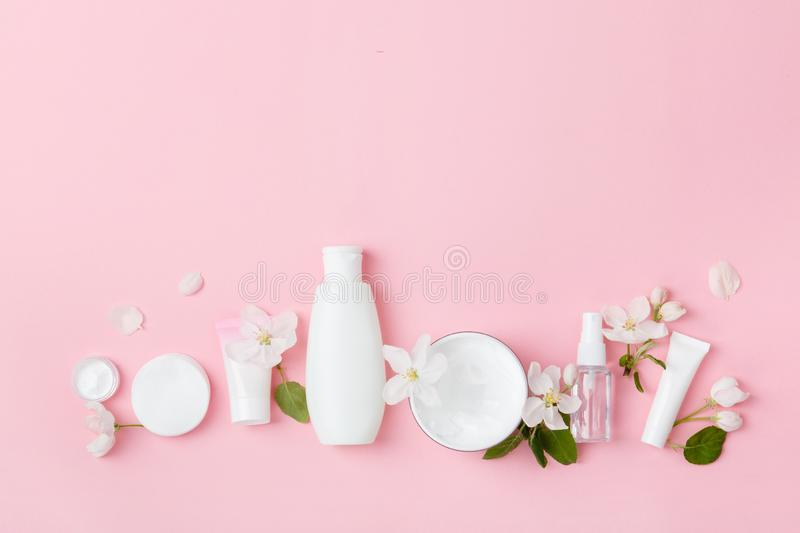 Face care products tonic or lotion, serum, cream, micellar water, cotton pads, shaver on pink background with spring apple bloss. Om. Freshness natural anti-age stock image