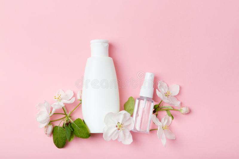 Face care products tonic or lotion, serum, spray, micellar water on pink background with spring apple blossom. Freshness natural anti-age care. Female everyday royalty free stock images