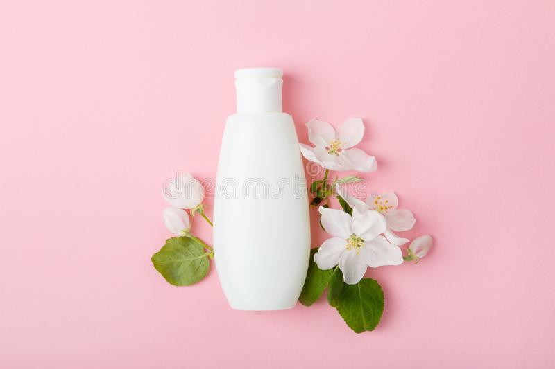 Face care products tonic or lotion, serum, spray, micellar water on pink background with spring apple blossom. Freshness natural anti-age care. Female everyday stock photo