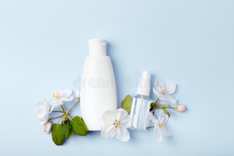 Face care products tonic or lotion, spray on blue background with spring apple blossom. Freshness natural anti-age care. Female everyday fresh cosmetics stock photography