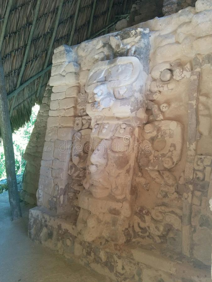 Face carved in stone in Mayan ruins. Face and symbols carved in stone under a protective thatched roof in Kohunlich Mayan ruins, in Quintana Roo, Mexico stock images
