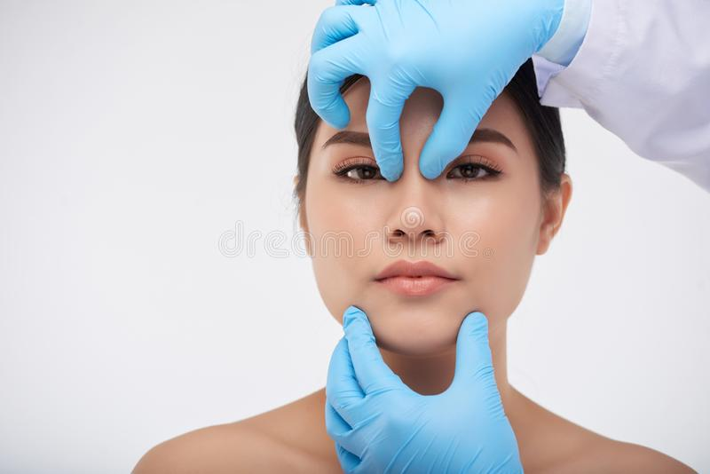 Face check before surgery. Hands of surgeon checking face construction of young Asian woman stock image