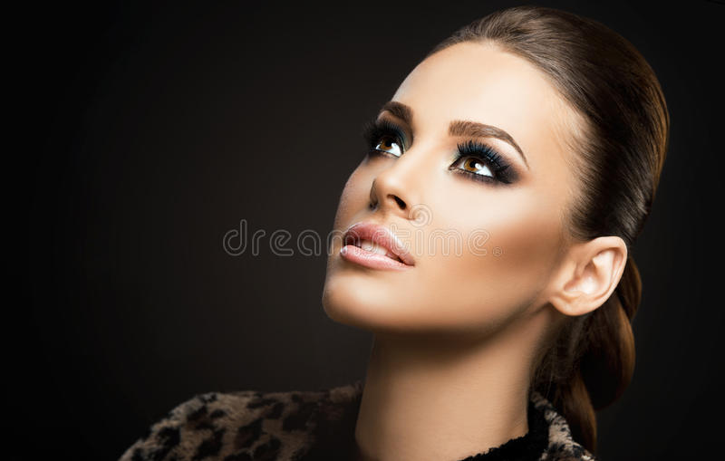 Face close-up of a beautiful young woman isolated on dark background; perfect skin, beauty portrait stock photos