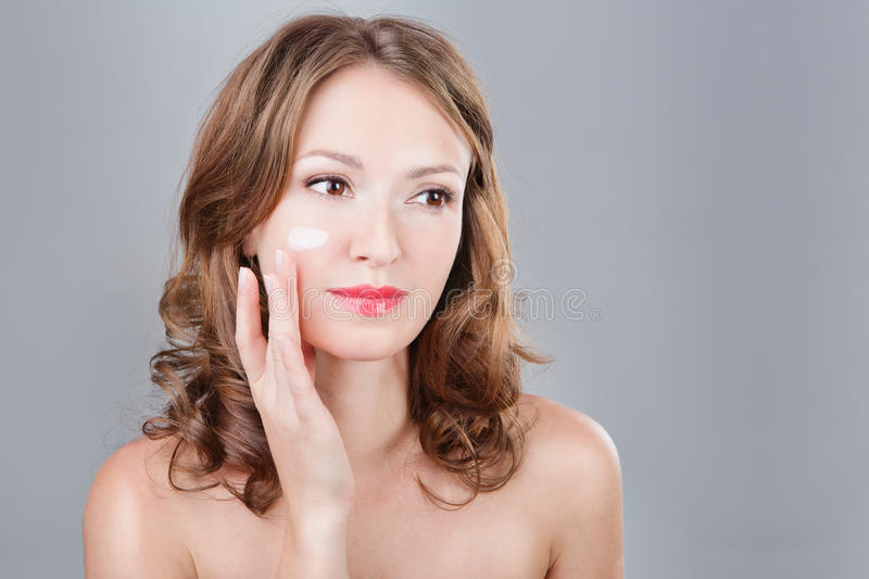 Face cream. Beautiful woman applying cosmetic cream on face on a cheek. Portrait of young woman applying moisturizer cream on her pretty face. Grey background stock photos