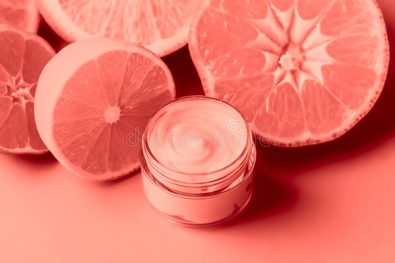 Face cream and citrus on a bright blue background. Toning living coral royalty free stock photo