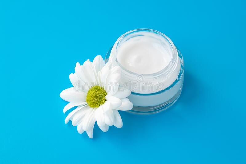 Face cream jar with white chamomile flower on blue background. Herbal lotion in glass bottle, natural cosmetic. Skin care concept. Moisturizer stock photography