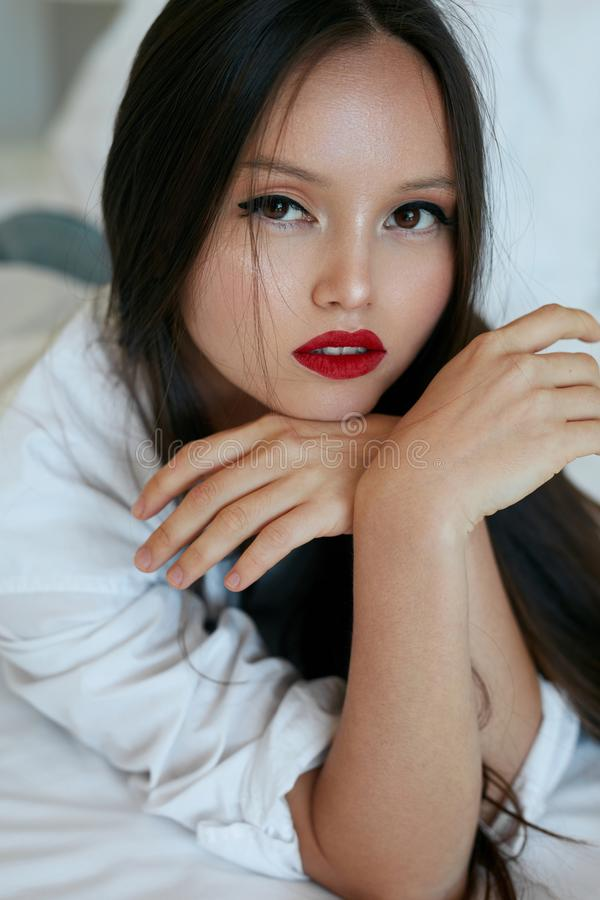 Face da mulher da beleza Modelo asiático bonito com composição vermelha dos bordos imagem de stock