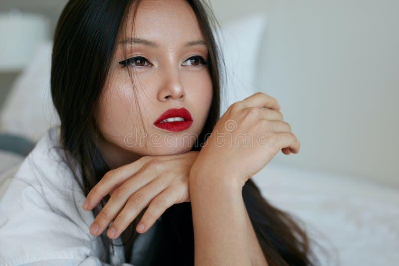 Face da mulher da beleza Modelo asiático bonito com composição vermelha dos bordos fotos de stock