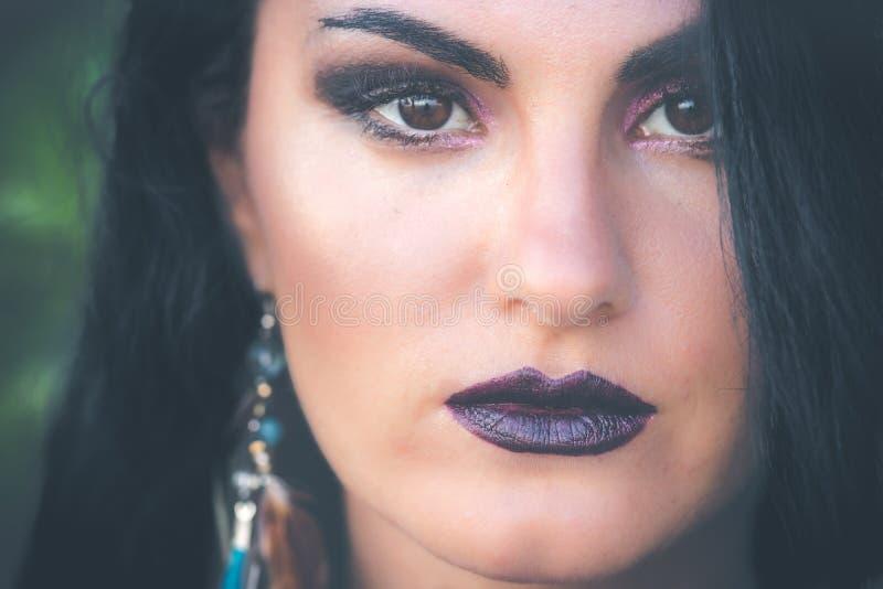 Face da mulher da beleza Retrato da fêmea nova 'sexy' bonita com composição preta facial perfeita, fundo verde exterior foto de stock