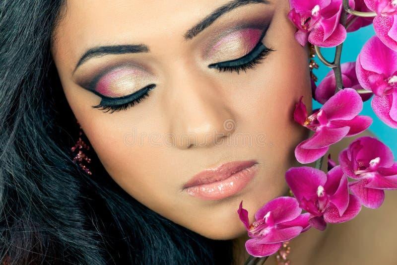 Face da mulher bonita com flores da orquídea fotografia de stock royalty free