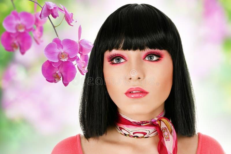 Face da mulher com flores da orquídea foto de stock