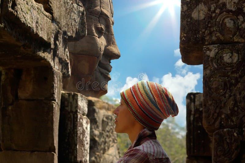 Face da mulher no fundo da cabeça de pedra fotografia de stock