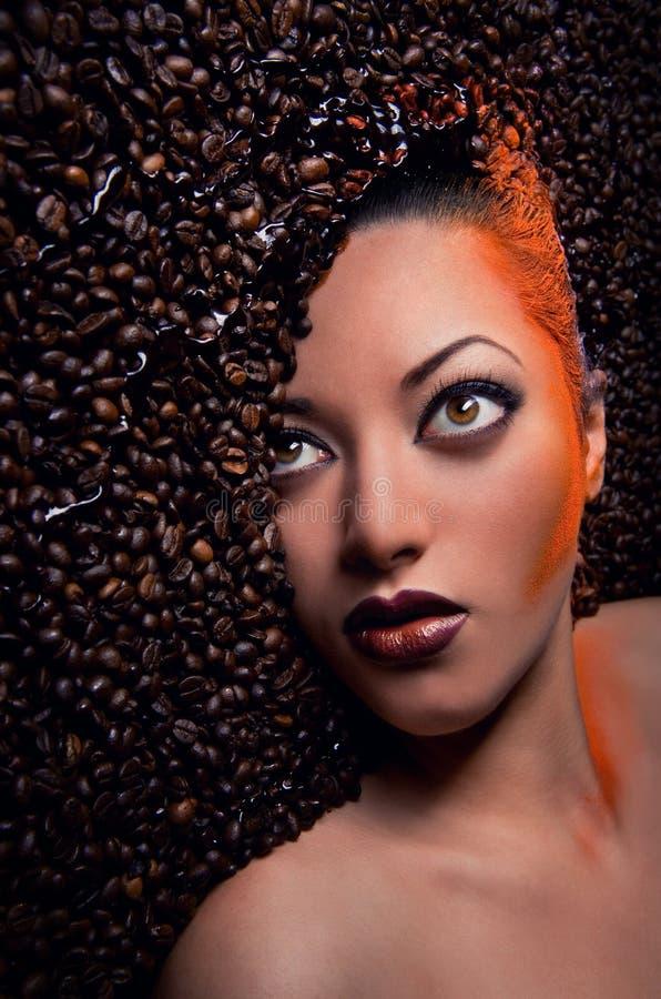 Face da mulher sobre feijões de café imagem de stock