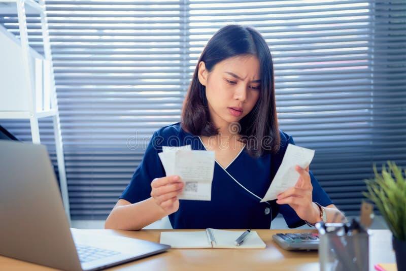 Face de tensão a mulher asiática que mantém a fatura das despesas e o cálculo das faturas das dívidas mensalmente à mesa do escri fotos de stock