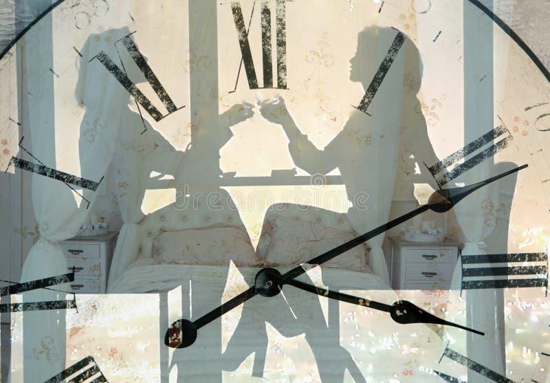 Face do relógio no fundo das silhuetas de duas mulheres com vidros de vinho imagens de stock royalty free