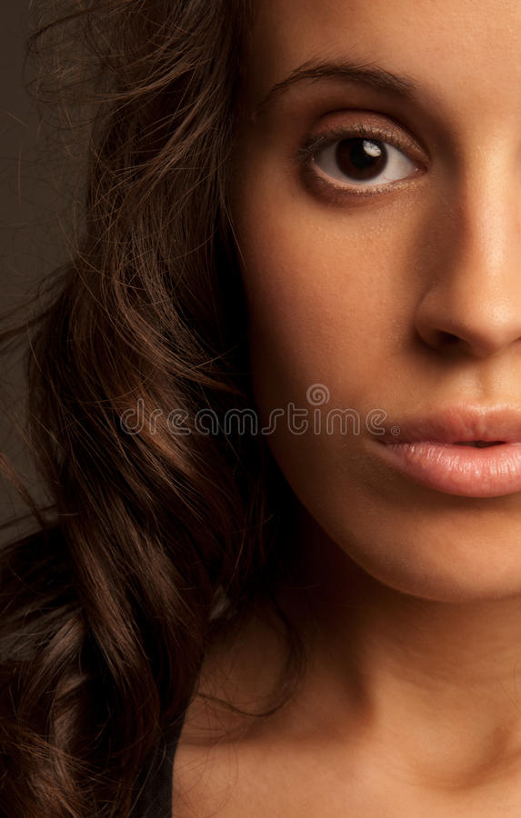 Face do retrato do close-up da mulher nova meia na obscuridade fotografia de stock royalty free