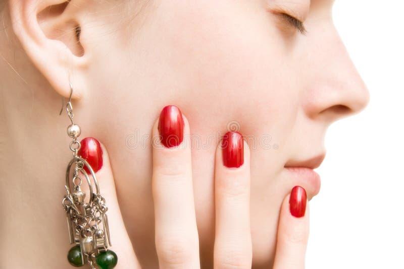 Face e mão da mulher nova com pregos vermelhos foto de stock royalty free