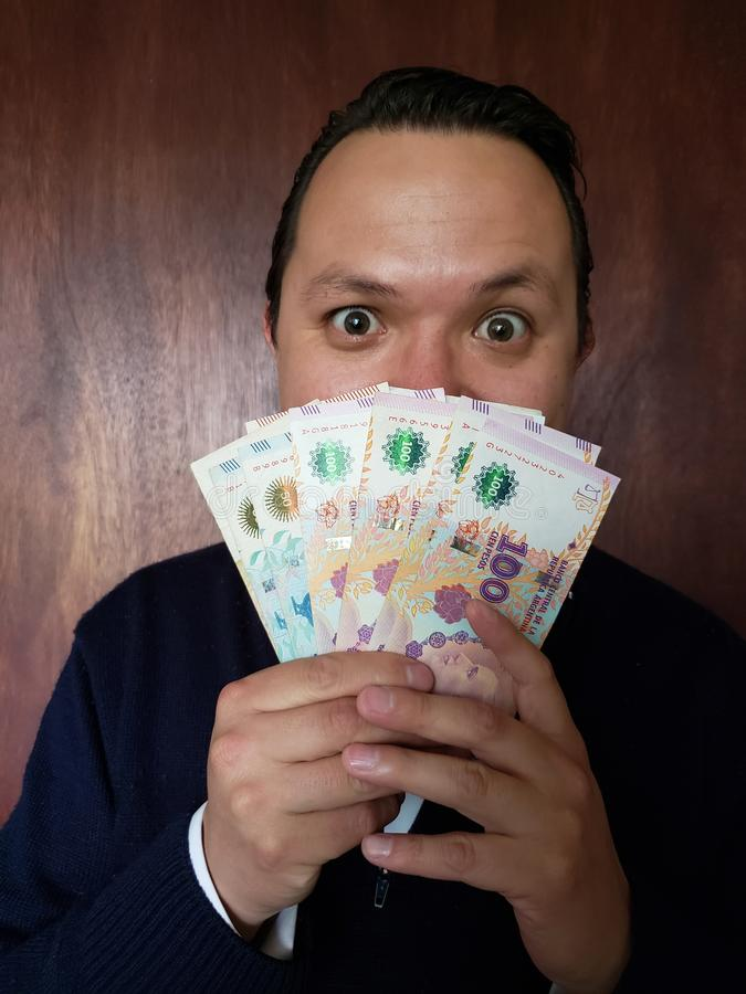 face with emotion expression of a young man with argentinean banknotes stock photos