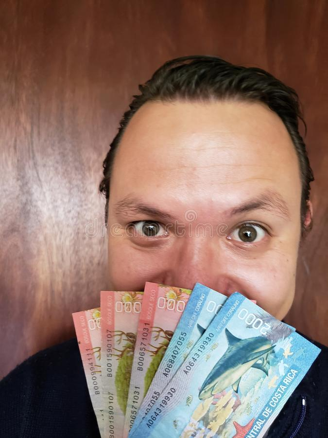 face with emotion expression of a young man with Costa Rican banknotes royalty free stock photos