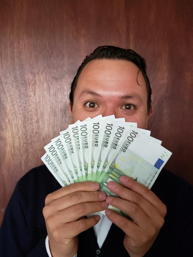face with emotion expression of a young man with European banknotes stock image