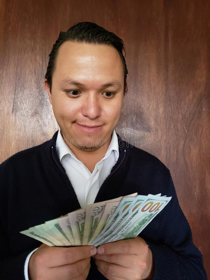 Face with emotion expression of a young man and holding american banknotes. Commerce, exchange, trade, trading, value, buy, sell, profit, price, rate, cash royalty free stock images