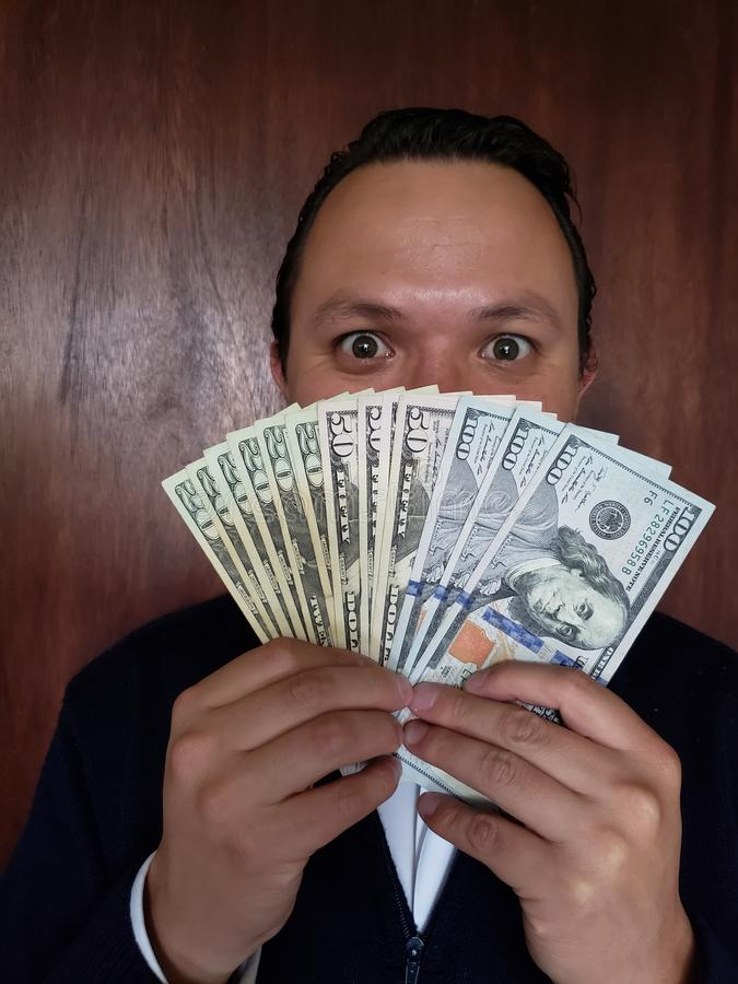 Face with emotion expression of a young man and holding American banknotes. Commerce, exchange, trade, trading, value, buy, sell, profit, price, rate, cash stock images