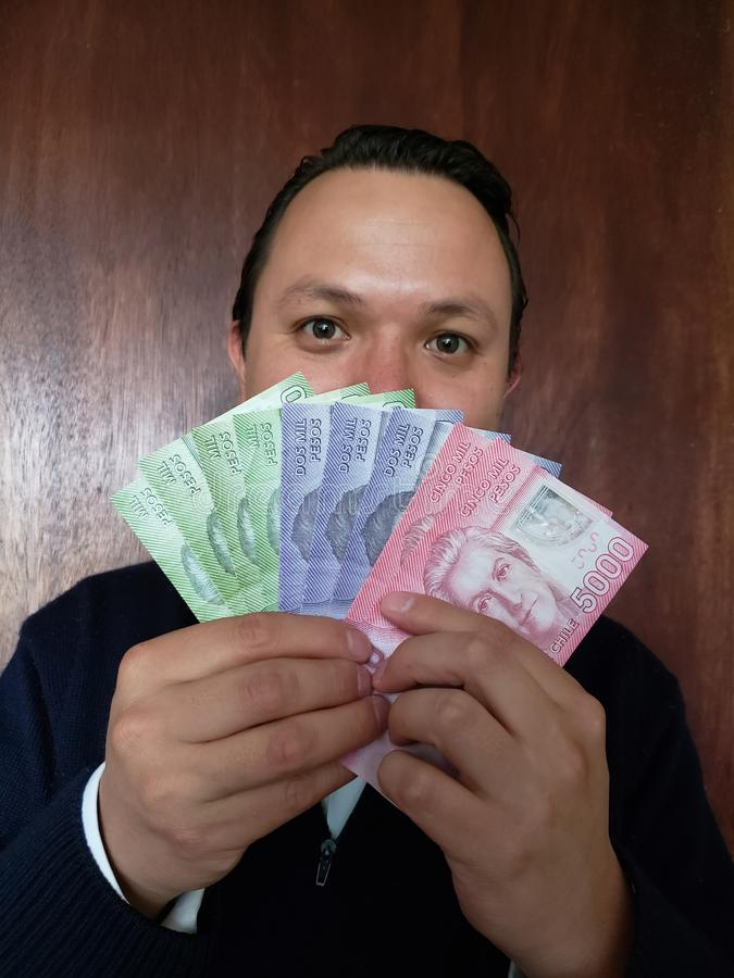 face with emotion expression of a young man and holding chilean banknotes stock image