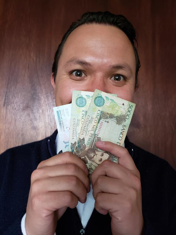 face with emotion expression of a young man and holding colombian banknotes royalty free stock photos