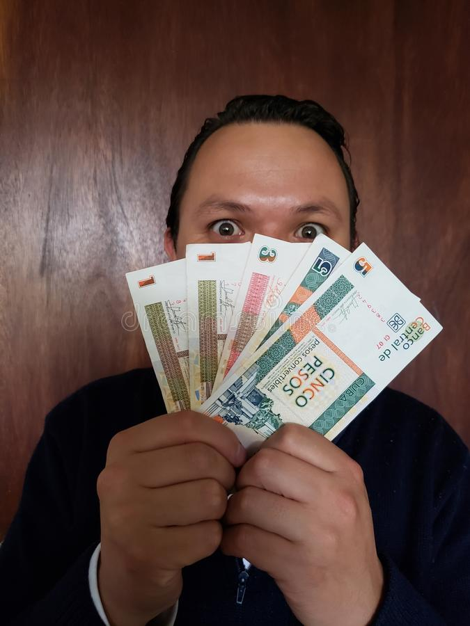 face with emotion expression of a young man and holding cuban banknotes royalty free stock images