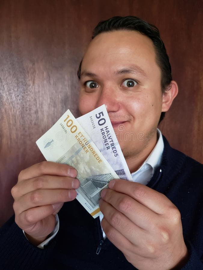 face with emotion expression of a young man and holding danish banknotes stock photography