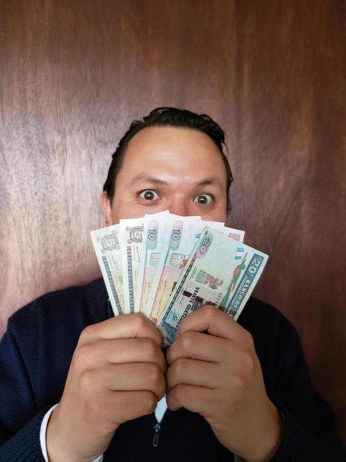 face with emotion expression of a young man and holding guatemalan banknotes royalty free stock image