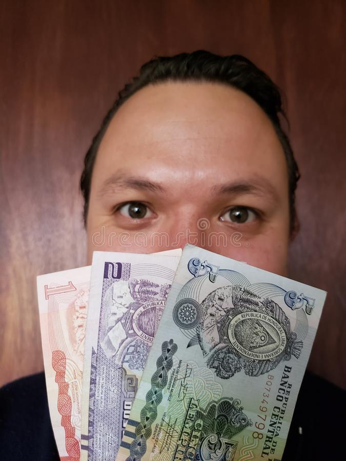 face with emotion expression of a young man with honduran banknotes stock images