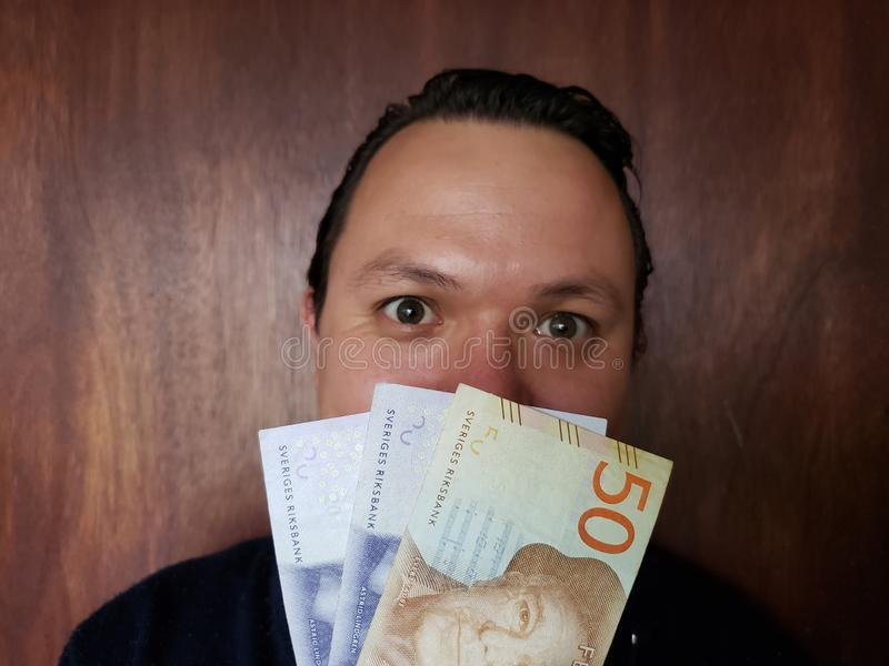 face with emotion expression of a young man and swedish banknotes royalty free stock photography