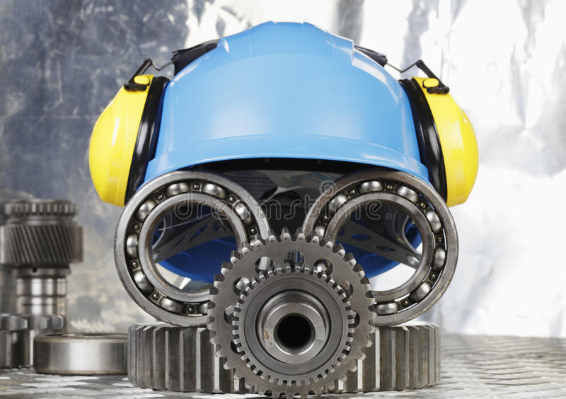 Face of engineering concept. Workers hardhat, earmuffs, engineering and machine parts, gears and bearings, conceptual image stock photo