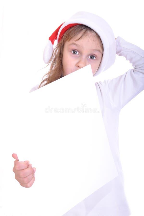 Face engraçada da criança que desgasta o hubcap vermelho de Santa?s imagem de stock