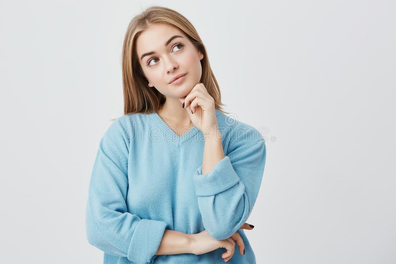 Face expressions and emotions. Thoughtful young pretty girl in blue sweater holding hand under her head, having doubtful stock image