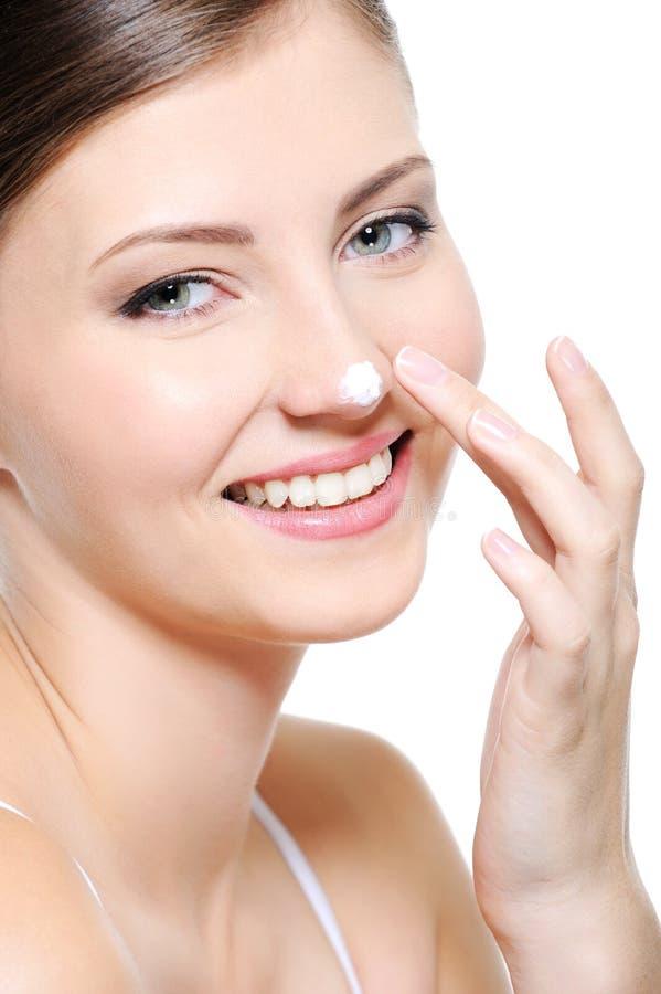 Face fêmea de sorriso com gota de um creme no nariz foto de stock