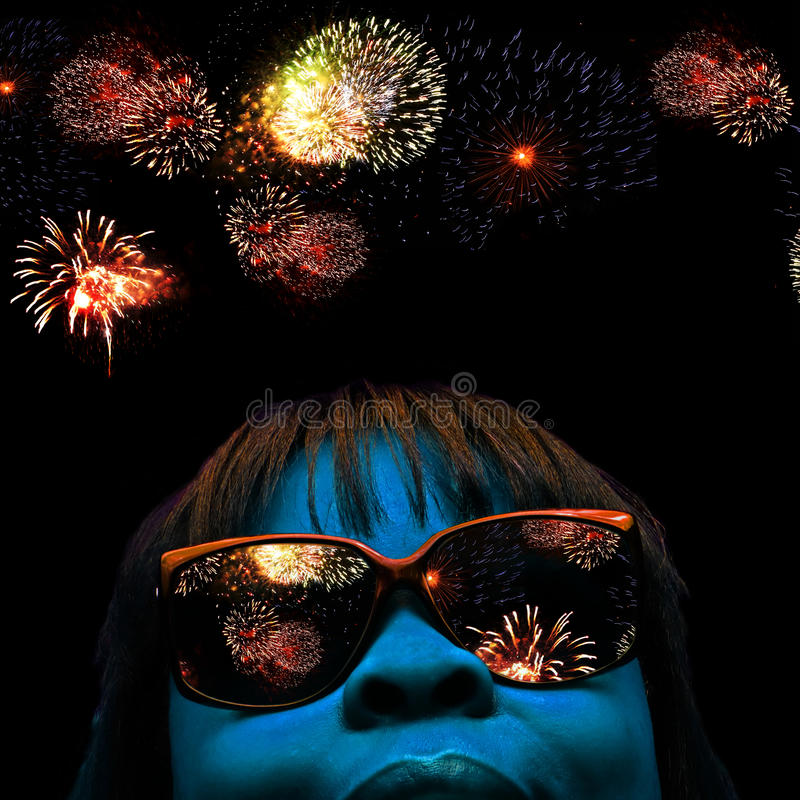 Face and fireworks. Stylized facial portrait of a blue faced female with fireworks over head and reflecting off her shades stock images