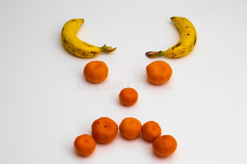 Face from fruits on white background. face made with fresh fruits. banana, mandarin tangerine royalty free stock photo
