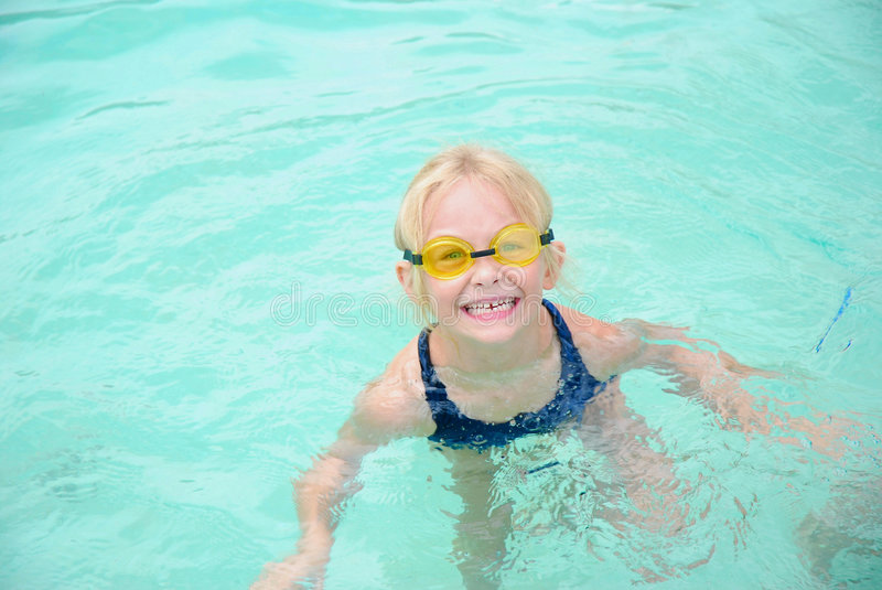 Face funny little swimmer. Outdoor portrait of a cute little blond caucasian girl child with funny smiling facial expression wearing yellow goggles while playing stock images