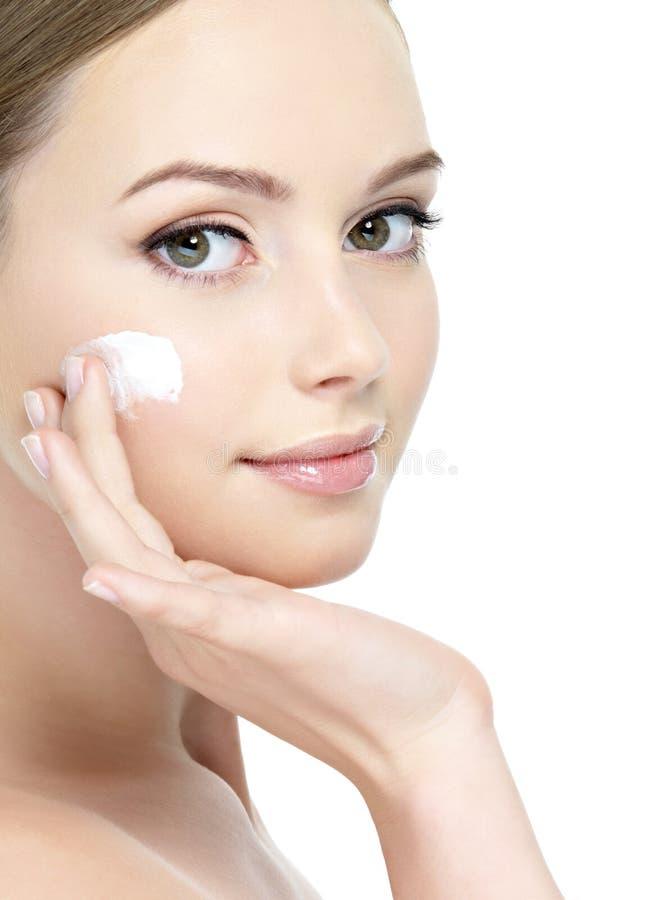 Face of girl applying cream stock photos