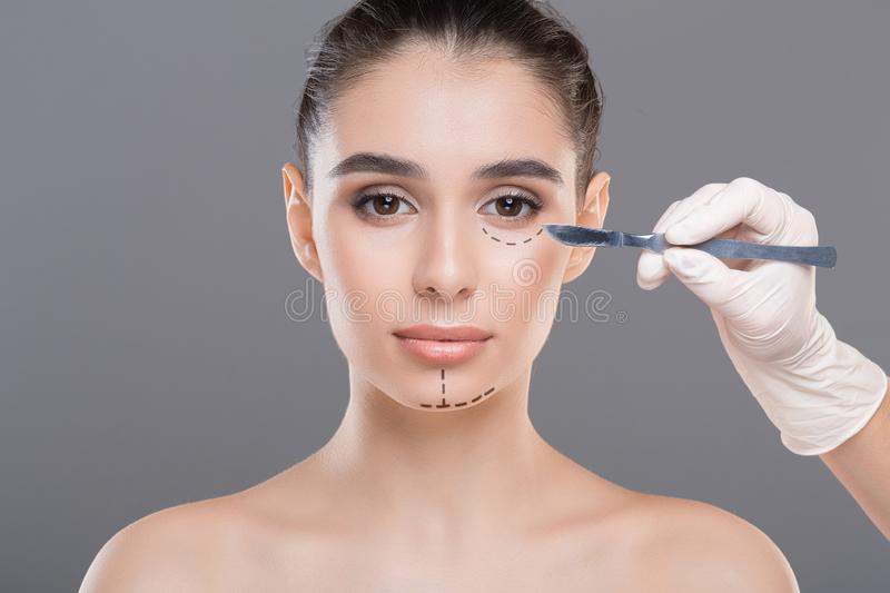 Doctor marking woman face before treatment procedure. Face lifting concept. Doctor marking woman face before treatment procedure stock photo