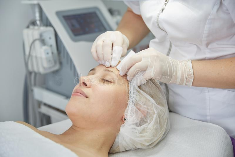 Face Lifting. Young woman getting facial massage in the cosmetology salon stock images