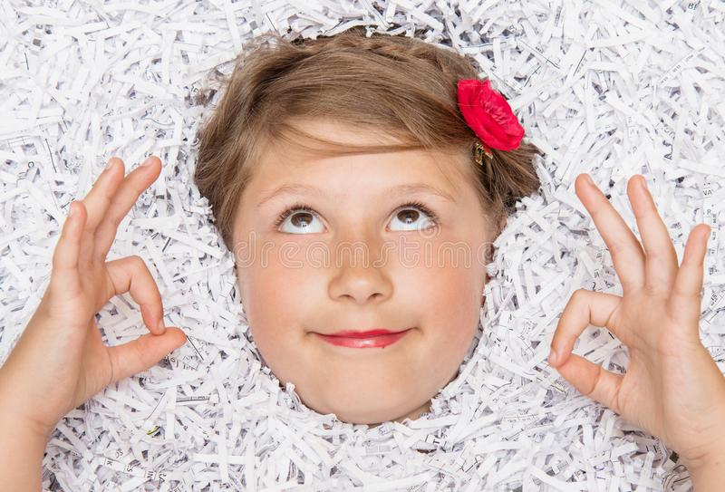 Face of a little girl emerging from a mountain of torn paper while doing yoga. A face of a little girl emerging from a mountain of torn paper while doing yoga stock photography
